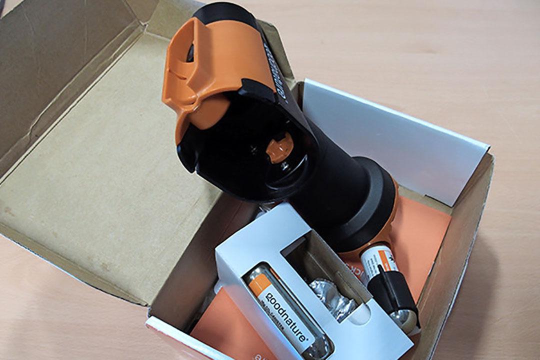 De muizenval van Merulin. De zwarte 'dop' boven aan bevat de lokstof. De val wordt opgehangen aan de oranje houder. Zichtbaar is de oranje kunststof staaf die de neklag geeft. Rechts beneden zit de gaspatroon die voor de druk zorgt. - Foto: Stan Verstegen
