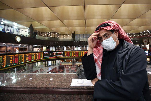 Een handelaar op de Boursa Kuwait in Koeweit draagt een mondkapje tegen het coronavirus. - Foto: AFP