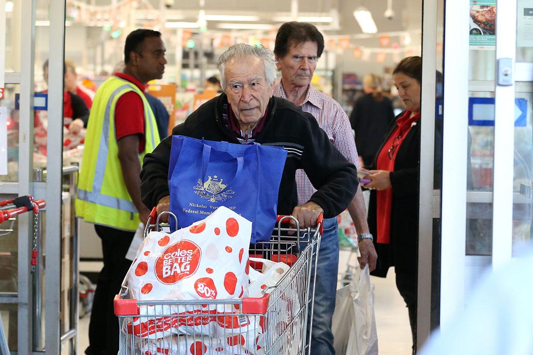 Een klant verlaat de Australische supermark Coles met een kar vol boodschappen. - Foto: ANP