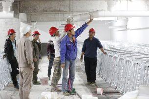 Chinese arbeiders werken aan varkensstal. - Foto: Henk Riswick
