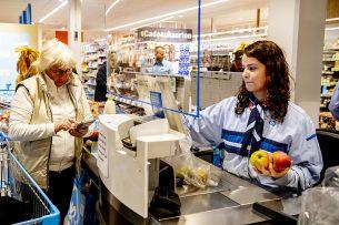 De medewerkers van een filiaal van Albert Heijn werken achter plexiglas. De maatregel moet voorkomen dat het coronavirus verder verspreid wordt. Foto: ANP