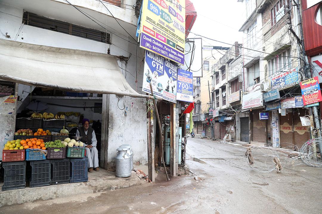 Een fruitverkoper wacht op klanten in zijn shop. De prijzen in India kelderen en het transportsysteem ligt na veertig dagen van lockdown in duigen. Foto: ANP