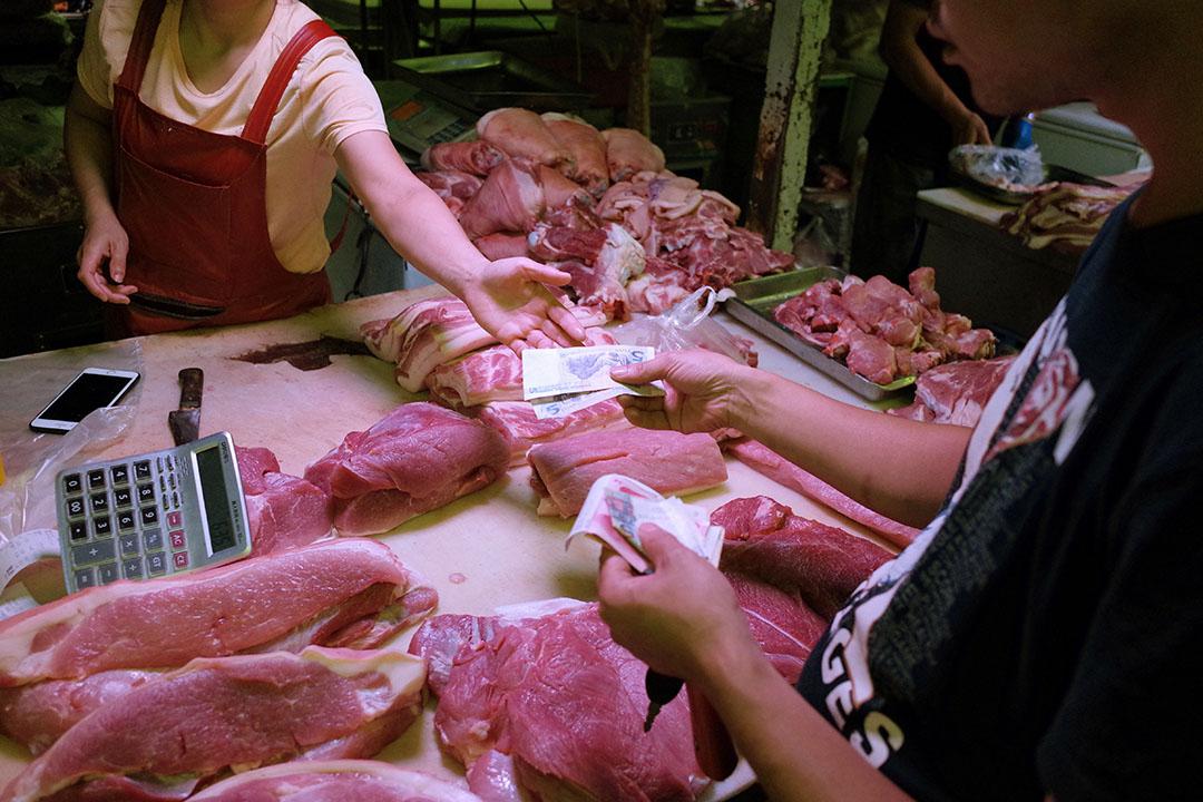 Verkoop van varkensvlees op een markt in Beijing. China blijft een hoofdrol spelen op de mondiale varkensvleesmarkt. Foto: ANP