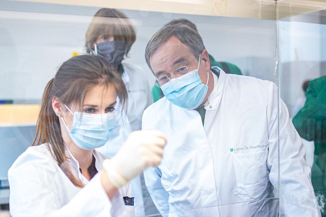 Minister-president Armin Laschet (r) van de deelstaat Noordrijn-Westfalen tijdens een bezoek aan een laboratorium waar coronatesten worden uitgevoerd. - Foto: EPA