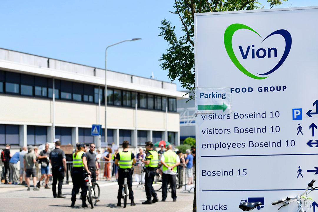 Demonstranten bij slachterij Vion in Boxtel (N.-Br.) vrijdagmiddag 26 juni. De politie houdt een oogje in het zeil. - Foto: ANP