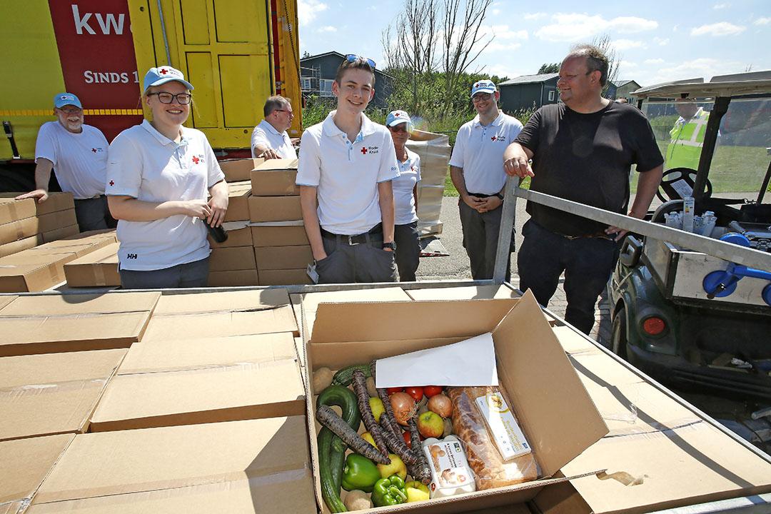 Medewerkers van het Rode Kruis en rechts Bart Plaatje van FNV klaar voor het rondbrengen van de boxen bij arbeidsmigranten in Zeewolde. - Foto: Ton Kastermans