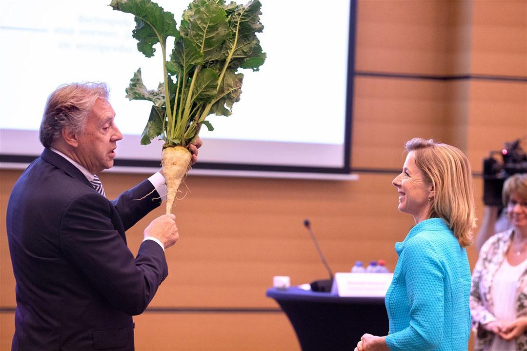 In de Raadzaal van de SER heeft staatssecretaris Stientje van Veldhoven het advies Biomassa in balans ontvangen. Van Ed Nijpls kreeg de staatssecretaris een suikerbiet. Rechts SER-voorzitter Mariette Hamer. Foto: ANP