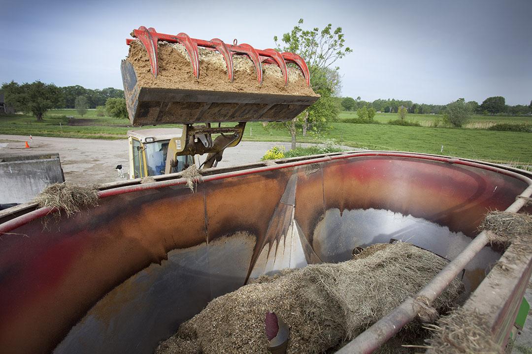 Een shovel schept vochtrijk mengvoer, waaronder bierbostel, in een voermengwagen. - Foto: Jan Willem Schouten