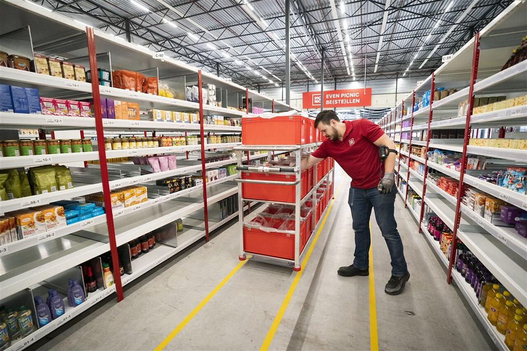 Een medewerker verzamelt producten in de schappen van het distributiecentrum van de online supermarkt Picnic. - Foto: ANP