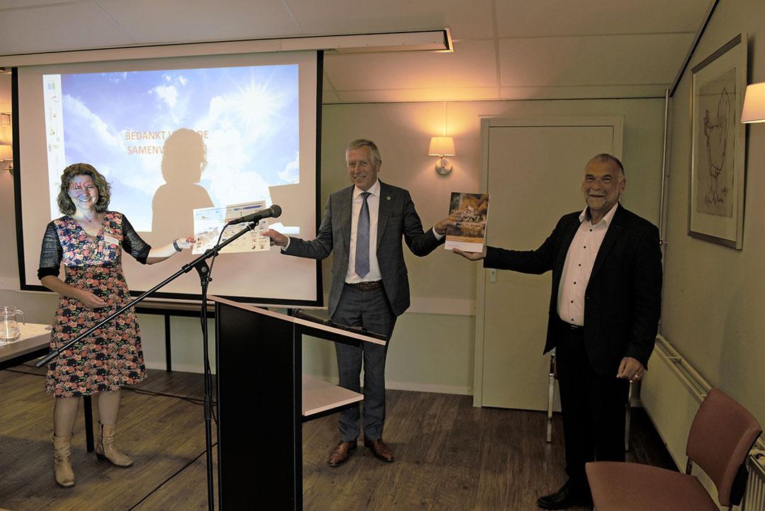 Wethouder Aart de Kruif van Barneveld krijgt het eerste exemplaar van het eindrapport van het onderzoek naar emissiereductie van projectleider Jan Workamp (rechts) en Regina Jansen, beleidsmedewerkers van de gemeente Ede (links). - Foto: Iepe Leeman