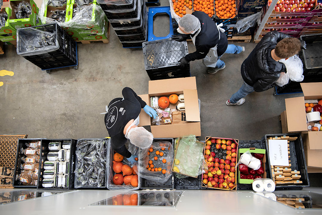 Medewerkers van Support Your Locals pakken voedselboxen in met producten die vanwege de coronacrisis niet meer afgezet kunnen worden aan de horeca. - Foto: Olaf Kraak/ANP