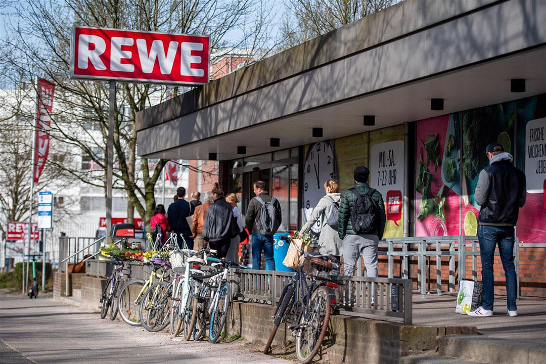 Een wachtrij bij een Rewe-filiaal in Hamburg. Rewe is één van de grootste supermarkten in Duitsland. - Foto: ANP