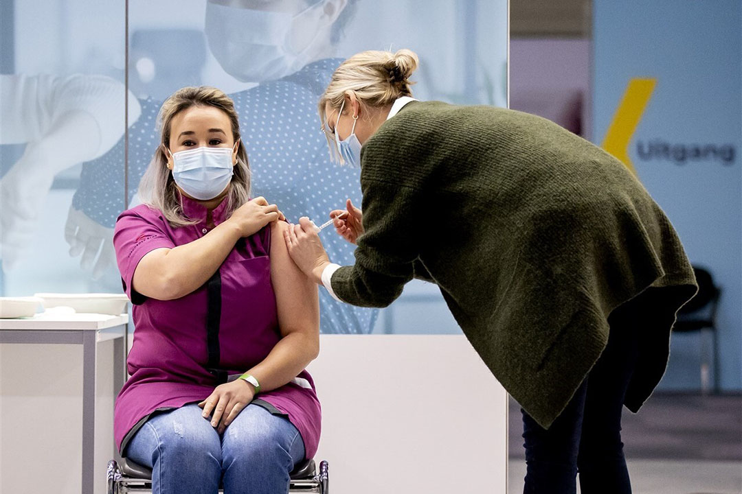 Sanna Elkadiri, medewerkster van verpleeghuis Het Wereldhuis, krijgt het eerste vaccin tegen het coronavirus. De regelbrij zie je nu ook terug bij het vaccinatieprogramma. Foto: ANP