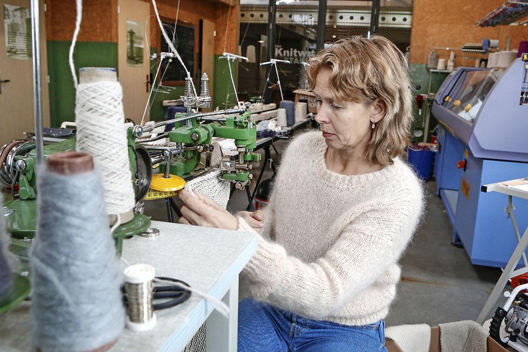 Met een linking machine zet ze de losse gebreide panden van truien en mutsen in elkaar. Achter Ovinge staat een nieuwe blauwe breimachine waarmee ze truien niet in 10 uur, maar in 3,5 uur breit.