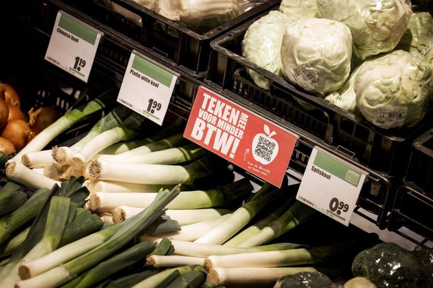Een actiebordje voor minder btw tussen het groente en fruit van supermarktketen Dirk van den Broek. De supermarktketen start een online petitie om de belasting op groente en fruit te verlagen. Foto: ANP