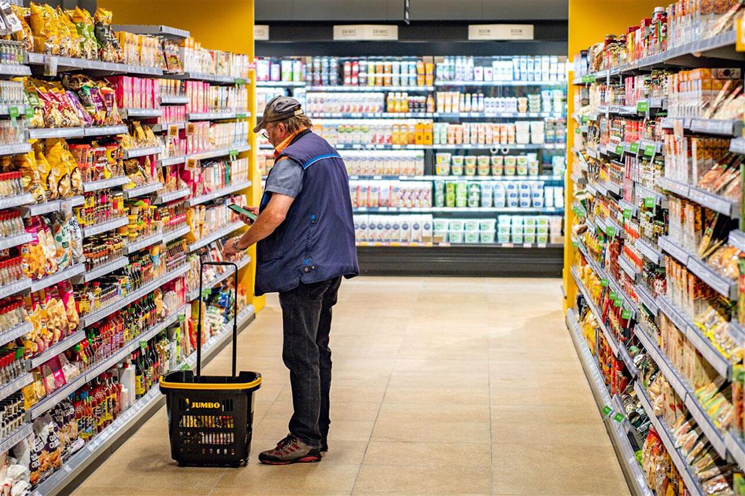 Een consument in een supermarkt. De volumegroei in de supermarkten is dit jaar groot. - Foto: ANP