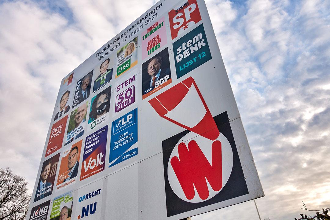 Verkiezingsbord met posters van politieke partijen die deelnemen aan de Tweede Kamer verkiezingen van 17 maart. PBL analyseerde de verkiezingsprogramma's. Foto: ANP