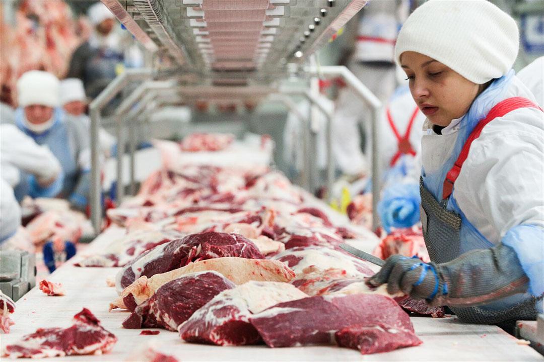 Een slager bezig met de verwerking vlees. - Foto: ANP