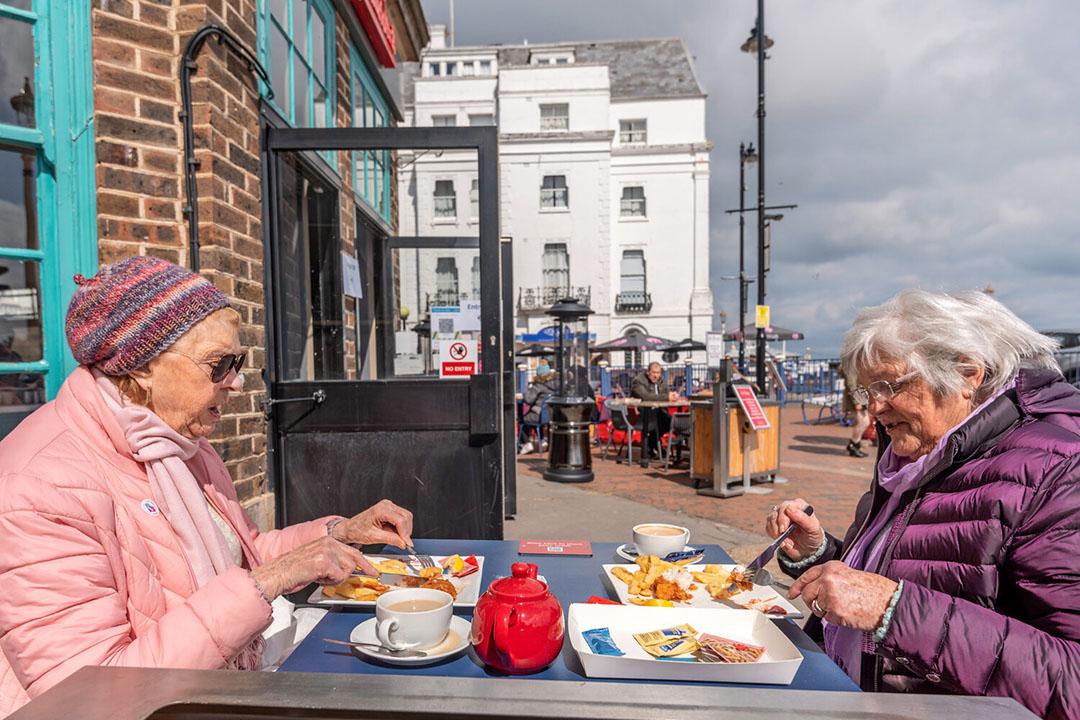 Een verjaardagsfeestje met fish en chips aan de Britse kust. De effectieve aanpak van de coronacrisis in Groot-Brittannië, waar veel Nederlandse frites heengaat, is veel relevanter dan versoepeling van de coronamaatregelen in Nederland. - Foto: ANP
