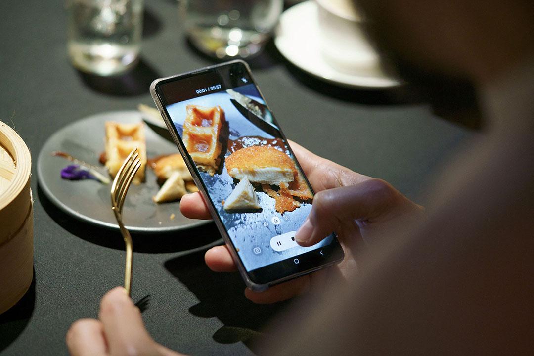 Een bezoeker van een restaurant in Singapore neemt een foto van 's werelds eerste kweekvleesproduct dat op de markt is. Singapore was eind vorig jaar het eerste land dat kweekvlees toestond. Foto: ANP