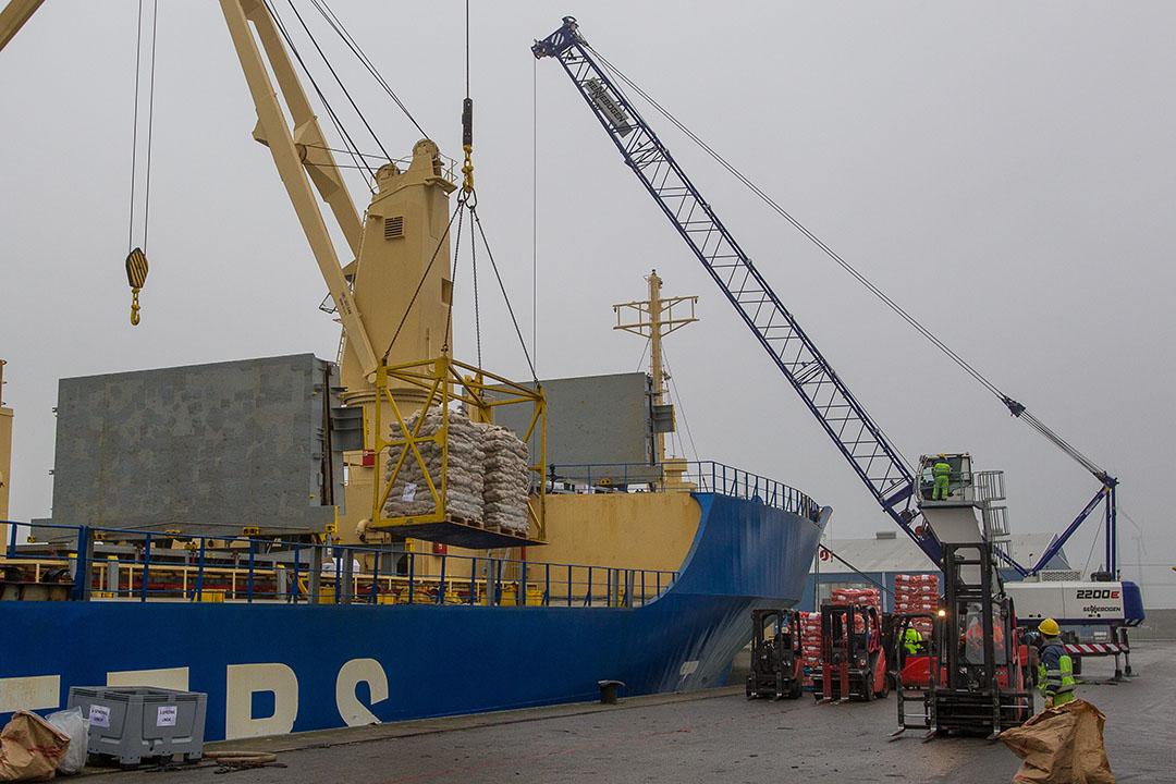 Uien worden geladen in de haven van Vlissingen. De kwaliteitscontroleur controleert de uien als ze op de boot geladen worden naar Afrika. - Foto: Peter Roek