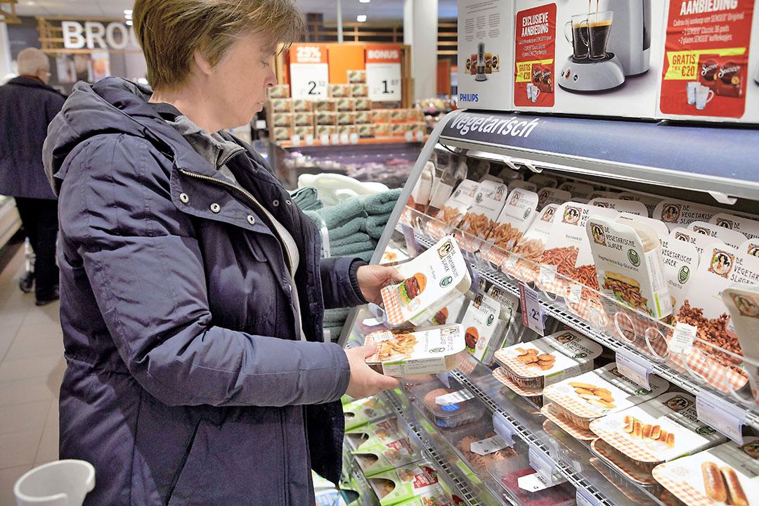 Vrouw bij het winkelschap met vleesvervangers. De verkoopwaarde van vlees- en zuivelvervangers nam in twee jaar 50% toe. Foto: ANP