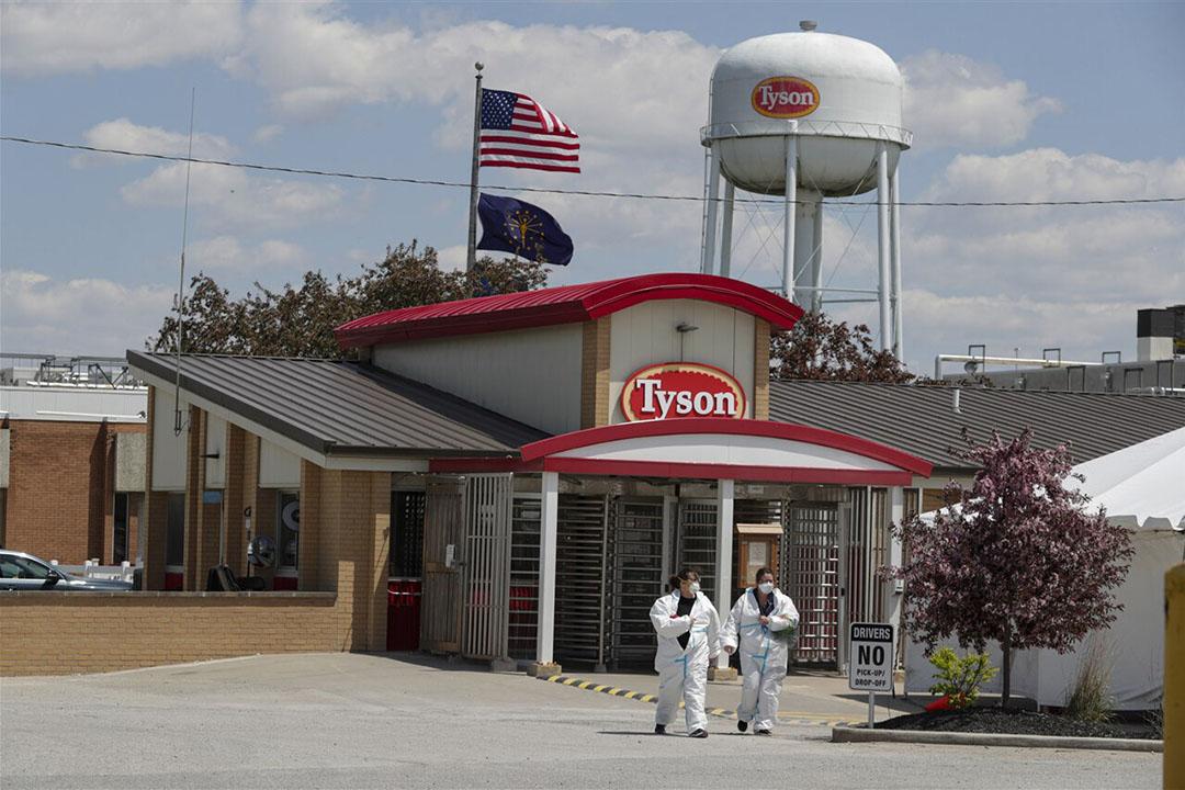 Twee medewerkers van Tyson Foods verlaten een locatie van de slachterij in de Verenigde Staten. - Foto: ANP