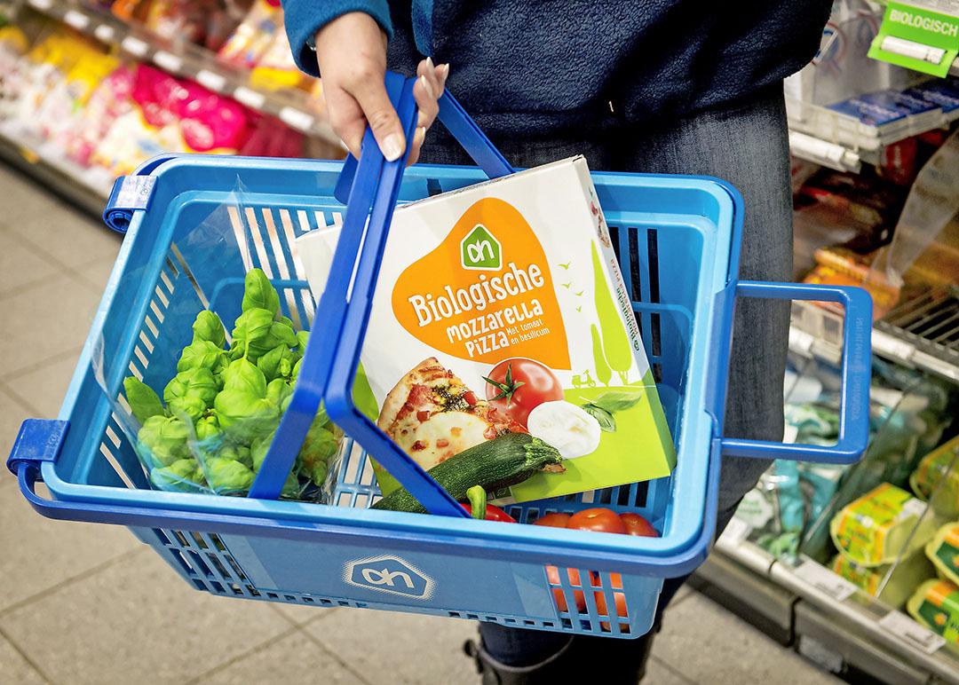 Biologische pizza in een winkelmandje. Biologische grondstoffen zijn vaak duurder dan gangbare. Foto: ANP