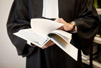 Bladeren in een juridisch naslagwerk. - Foto: Koos Groenewold